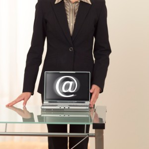 """Businesswoman With Laptop and """"At"""" Sign"""