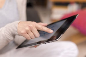 Woman hand touching screen on digital tablet.